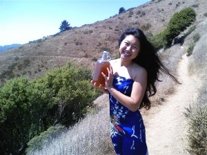 Rana Chang, owner and operator of House Kombucha, holds a growler of her beverage while standing on a hillside path in a blue dress.