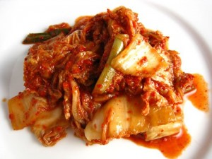 Red fermented and spicy Korean Kim Chi cabbage on a plate.