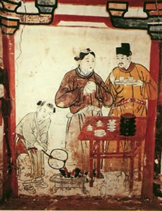 An old style Asian drawing of two men sampling tea while a woman or boy fans the fire.