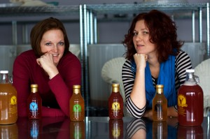 Vanessa Tortolano and Alla Shapiro of NessAlla Kombucha with 16oz bottles and growlers of their product.
