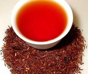 A cup of redbush rooibos tea sits atop a pile of roasted honeybush leaves and stems.