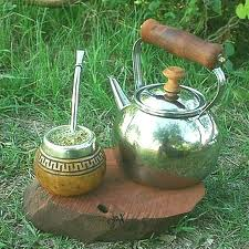 A gourd and bombilla (metal straw) used for drinking yerba mate sits atop a stone next to a kettle.