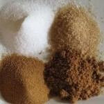 Four piles of different types of sugar on a table: White Sugar, Evaporated Cane Juice, Brown Sugar & Demerrera.